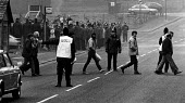 Miners Strike, 25 strike breaking miners leaving Silverwood Colliery (nr Rotherham) at the end of a shift. 150 pickets jeers from behind the police line. - John Sturrock - 1980s,1985,adult,adults,CLJ,coal,collieries,Colliery,cross,crosses,crossing,DISPUTE,DISPUTES,force,INDUSTRIAL DISPUTE,jeer,jeering,jeers,leaving,man men,mask masks masked,MATURE,member,member members,