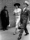 A homeless man looking at the wealthy arriving at Ascot Racecourse in 1981. - John Sturrock - ,&,1980s,1981,adult,adults,AFFLUENCE,AFFLUENT,ARRIVAL,arrivals,arrive,arrived,arrives,arriving,Ascot,Bourgeoisie,cities,City,Contrast,Contrasting,Couple,couples,dressed up,EBF Economy,elite,elitism,EQ