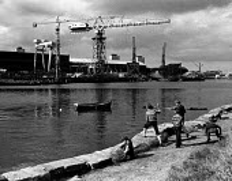 Children playing on the riverside infront of a shipyard, in Sunderland. Throwing stones into the river. - John Sturrock - ,1980,1980s,boat,boats,boy,boys,capitalism,capitalist,Child,CHILDHOOD,children,cities,City,crane,cranes,EBF,Economic,Economy,Industries,industry,juvenile,juveniles,kid,kids,LFL Leisure soi,maker,maker