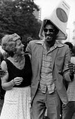 Notting Hill Carnival in 1981. - John Sturrock - 1980s,1981,ACE,ace culture,adult,adults,BAME,BAMEs,black,BME,BME Black minority ethnic,bmes,Carnival,Carnivals,Cigar,cigars,cities,city,Couple,couples,cultural,culture,dance,dancer,dancers,dancing,div