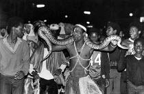 A snake handler at the Notting Hill Carnival, 1981. - John Sturrock - 1980s,1981,ACE,ace culture,adolescence,adolescent,adolescents,Animal,animals,BAME,BAMEs,Black,BME,BME Black minority ethnic,bmes,boy,boys,Carnival,Carnivals,child,CHILDHOOD,children,cities,city,cultur