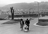 A family walking home, after a unsuccessful visit to the 'Job Shop' in Pontypridd, during the recession. - John Sturrock - 1970s,1979,adult,adults,babies,baby,Child,CHILDHOOD,children,cities,city,DAD,DADDIES,DADDY,DADS,DOWNTURN,EARLY YEARS,EBF Economy,economic,Economic Crisis,EQUALITY,estates,excluded,exclusion,families,f