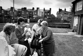 A mother with her child, talking to her neighbours. June 1989. - John Sturrock - 1980s,1989,adult,adults,age,aged,ageing population,babies,baby,carrier,carriers,child,CHILDHOOD,children,communicating,communication,communities,community,conversation,conversations,council estate,cou