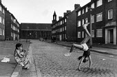 Children playing in the streets in Toxteth, Liverpool. - John Sturrock - ,1980s,1981,animal,animals,BAME,BAMEs,black,bme,BME Black minority ethnic,BME minority ethnic,bmes,canine,canines,cartwheel,cartwheels,child,CHILDHOOD,children,cities,city,communities,community,counci