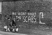 Children walk past graffiti We Wont Forget The Scabs and a scab hanging from a scaffold, bitterness remains at the end of the strike, Armthorpe, Yorkshire - John Sturrock - ,1980s,1985,breaker,breakers,breaking,child,CHILDHOOD,children,communities,community,cross,crosses,crossing,disapproval,disapproving,disputes,feeling,feelings,female,females,forget,girl,girls,Graffiti