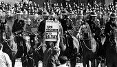 Picket holding a placard Turn Orgreave into Saltley (gates) as mounted officers get ready to charge the mass picket. Orgreave. - John Sturrock - 1980s,1984,adult,adults,animal,animals,Battle of Orgreave,BSC,CLJ,coke works,coking plant,DISPUTE,DISPUTES,domesticated ungulate,domesticated ungulates,equestrian,equine,force,horse,horse horses,horse