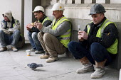 Construction workers on their lunch break sitting down together and having a chat. London. - Justin Tallis - 03-02-2010