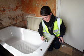 Apprentice working for her NVQ level 2 in plumbing, installing a bath in a bathroom. Nottingham City Homes, One In A Million Scheme. Nottingham. - Justin Tallis - 2010,2010s,a,apprentice,Apprentices,apprenticeship,at,bath,Construction Industry,developer,developers,development,Edu education,female,fitting,Homes,housing,install,installing,LAB LBR Work,maintaining