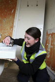 Apprentice working for her NVQ level 2 in plumbing, installing a bath in a bathroom. Nottingham City Homes, One In A Million Scheme. Nottingham. - Justin Tallis - 2010,2010s,a,apprentice,Apprentices,apprenticeship,at,bath,Construction Industry,developer,developers,development,Edu education,EMOTION,EMOTIONAL,EMOTIONS,enjoy,enjoying,ENJOYMENT,female,fitting,HAPPI