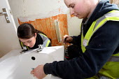 Apprentice working for her NVQ level 2 in plumbing, being helped to install a bath in a bathroom. Nottingham City Homes, One In A Million Scheme. Nottingham. - Justin Tallis - 2010,2010s,apprentice,Apprentices,apprenticeship,at,bath,class,communicating,communication,Construction Industry,developer,developers,development,Edu education,experience,Experienced,female,fitting,Ho