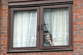 An elderly woman looking out from behind the net curtains of her window. London. - Justin Tallis - 05-04-2010