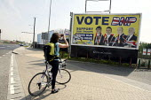 A cyclist stops to take a photograph of a defaced British National Party bring our troops home billboard by the side of the road in Barking. East London. - Justin Tallis - 2010,2010s,activist,activists,advert,ADVERTISED,advertisement,advertisements,advertising,ADVERTISMENT,adverts,against,army,billboard,billboards,bnp,british,British National Party,campaign,campaigner,c