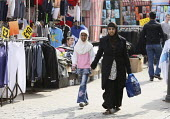 Shoppers going through the stalls at Barking Town Centre Market. East London. - Justin Tallis - &,2010,2010s,adult,adults,and,asian,BAME,BAMEs,belief,Black,BME,BME Black Minority Ethnic,bmes,bought,buy,buyer,buyers,buying,buys,child,CHILDHOOD,children,cities,city,commodities,commodity,communitie