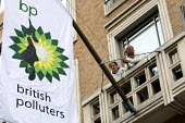 Greenpeace protesters on a balcony at BP headquarters hang a flag saying British Polluters in protest at the BP oil spill in the Gulf of Mexico. St James's Square, London. - Justin Tallis - 2010,2010s,action,activist,activists,against,bp,british,CAMPAIGN,campaigner,campaigners,CAMPAIGNING,CAMPAIGNS,civil disobedience,DEMONSTRATING,DEMONSTRATION,DEMONSTRATIONS,direct,energy,ENI environmen