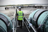 A worker walks between water transfer pipes at Thames Gateway Water Treatment Works. It is first plant of its kind to be built in the UK converting brackish water from the River Thames into clean drin... - Justin Tallis - 17-06-2010