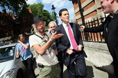 David Miliband MP walking away after he is confronted by an anti war protester against the complicity of Labour in the wars in Iraq and Afghanistan. Westminster London. - Justin Tallis - ,2010,2010s,activist,activists,against,anti,Anti War,Antiwar,CAMPAIGN,campaigner,campaigners,CAMPAIGNING,CAMPAIGNS,confront,confrontation,confronted,confronting,DEMONSTRATING,demonstration,DEMONSTRATI