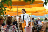 Waitress serving racegoers at Venue Cliquot champagne bar. Goodwood racecourse. - Justin Tallis - 2010,2010s,AFFLUENCE,AFFLUENT,alcohol,bored,bottle,bottles,Bourgeoisie,cash,champagne,Champagne Bottle,CHAMPAIGN,course,courses,drink,drinker,drinkers,drinking,EARNINGS,elite,elitism,EQUALITY,fed,fema