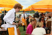 Waiter serving racegoers at Venue Cliquot champagne bar. Goodwood racecourse. - Justin Tallis - 2010,2010s,AFFLUENCE,AFFLUENT,alcohol,bored,bottle,bottles,Bourgeoisie,champagne,Champagne Bottle,CHAMPAIGN,course,courses,drink,drinker,drinkers,drinking,EARNINGS,elite,elitism,EQUALITY,fed,glass,hig
