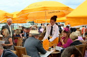 Waitress serving racegoers at Venue Cliquot champagne bar. Goodwood racecourse. - Justin Tallis - 2010,2010s,AFFLUENCE,AFFLUENT,alcohol,bored,bottle,bottles,Bourgeoisie,champagne,Champagne Bottle,CHAMPAIGN,course,courses,drink,drinker,drinkers,drinking,EARNINGS,elite,elitism,EQUALITY,fed,glass,hig
