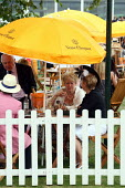 Racegoers enjoying themselves at Venue Cliquot champagne bar. Goodwood racecourse. - Justin Tallis - 2010,2010s,AFFLUENCE,AFFLUENT,alcohol,bottle,bottles,Bourgeoisie,champagne,Champagne Bottle,CHAMPAIGN,course,courses,drink,drinker,drinkers,drinking,elite,elitism,enjoying,ENJOYMENT,EQUALITY,high,high