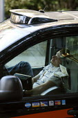 Exhausted taxi driver having getting some sleep whilst pulled over at the side of the road in his cab. His A-Z street guide of London is next to him. - Justin Tallis - 16-08-2010
