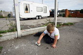 Traveller boy loading stones onto his toy truck. Travellers are removed by bailiffs from their pitch of land, which they legally own, after the council served an eviction notice. Hovefields Drive in B... - Justin Tallis - 07-09-2010