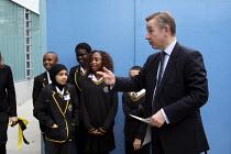 Michael Gove MP shaking hands with school children on a visit to the Globe Academy in Southwark, South London. - Justin Tallis - 2010,2010s,academies,Academy,adolescence,adolescent,adolescents,ark,BAME,BAMEs,Black,BME,bmes,child,CHILDHOOD,children,cities,city,CONSERVATIVE,Conservative Party,conservatives,diversity,edu,edu educa