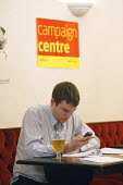 Last minute telephone calling at the Labour Party campaign centre on the night of the 2010 General Election. Croydon. - Justin Tallis - 2010,2010s,Alcohol,beer,call,calling,calls,campaign,campaigning,CAMPAIGNS,CANVASING,canvassing,CELLULAR,centre,communicating,communication,DEMOCRACY,drink,drinking,election,elections,EXHAUSTED,EXHAUST