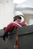 A workman leaning over a temporary wall in the snow. London. - Justin Tallis - 30-11-2010