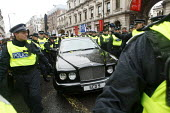 Police form a guard around a Bentley Arnage car, worth around a quarter of a million pounds, after the driver tried to barge his was through an impromptu march by students who walked out in protest ag... - Justin Tallis - 30-11-2010