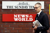 A man leaving News International passes The Sunday Times and News of The World signs, with a copy of the News of the World. Wapping, London. - Justin Tallis - 08-07-2011