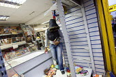 Goods are taken from a small shop in Hackney after it was broken into during rioting - Justin Tallis - 08-08-2011