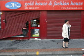 After the looting. A women looks at damaged shops after rioting and looting spread to many places in London, and around England, after Mark Duggan, 29, was killed by police on Thursday. Croydon. - Justin Tallis - 09-08-2011