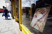 Dalston high street photographic shop with a photograph depicting an idealised happy family. East London. - Justin Tallis - 13-08-2011