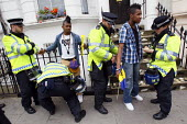 Police stop and search young black men on mass at Notting Hill Carnival. London. - Justin Tallis - 2010s,2011,adult,adults,and,BAME,BAMEs,black,BME,BME Black Minority Ethnic,bmes,check,checking,checks,cities,city,CLJ,cultural,diversity,ethnic,ethnicity,evidence,FEMALE,force,harassment,id,identifyin