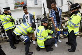 Police stop and search young black men on mass at Notting Hill Carnival. London. - Justin Tallis - ,2010s,2011,adult,adults,and,BAME,BAMEs,black,BME,BME Black Minority Ethnic,bmes,check,checking,checks,cities,city,CLJ,cultural,diversity,ethnic,ethnicity,evidence,FEMALE,force,harassment,id,identifyi