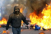 A masked protester walks past a burning barricade during the eviction of Dale Farm. Basildon. Essex. - Justin Tallis - 19-10-2011