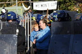 A woman holding her child stands near riot police as they start the eviction process. The eviction of Dale Farm. Basildon. Essex. - Justin Tallis - ,2010s,2011,activist,activists,adult,adults,babies,baby,BAME,BAMEs,BME,bmes,CAMPAIGN,campaigner,campaigners,CAMPAIGNING,CAMPAIGNS,child,CHILDHOOD,children,CLJ,DEMONSTRATING,DEMONSTRATION,DEMONSTRATION