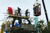 Riot police in a cherry picker, and bailiffs in a cage, descend on a tower barricade to remove protesters who are refusing to come down. The eviction of Dale Farm. Basildon. Essex. - Justin Tallis - 19-10-2011