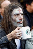 Drinking a cup of Starbucks coffee. Occupy London Stock Exchange protest camp. St Paul's, London. - Justin Tallis - 01-11-2011