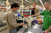 Customer paying for shopping using a chip and pin security machine, Asda, Newport, South Wales - Justin Tallis - 23-11-2004