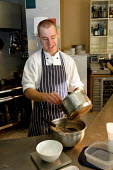 Chef making chocolate fondant - Justin Tallis - chefs, cooks, foods, pouring, restaurants, worker, working, works,2000s,2004,Apron,catering,chef,CHEFS,Cook,COOKERY,Cooking,COOKS,EARNINGS,EBF Economy,EMOTION,EMOTIONAL,EMOTIONS,employee,employees,Emp