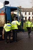 Police stop truck driver to check the weight of his trailer. Also they are checking the vehicles tachograph to make sure the driver isn�t exceeding 9 hours a day at the wheel. Caerleon, South Wales - Justin Tallis - 2000s,2005,adult,adults,beat,chart,charts,check,checking,CLJ crime law,driver,drivers,DRIVING,EARNINGS,EQUALITY,examination,examining,FEMALE,force,goods,HAULAGE,HAULIER,HAULIERS,heddlu,hgv,hgvs,highwa