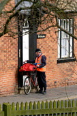 Postman delivering letters in the morning. Stratford Upon Avon - Justin Tallis - 2000s,2005,bag,bags,Bicycle,bicycles,BICYCLING,Bicyclist,Bicyclists,Bike,bikes,communicating,communication,communities,community,CYCLE,cycles,CYCLING,Cyclist,Cyclists,Deliver,deliveries,Delivering,Del