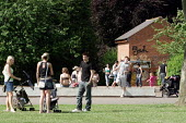 Young mothers with their parms speaking to a teenager in a park - Justin Tallis - 22-06-2005