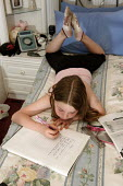 10 year old girl lying on a large double bed doing her school homework - Justin Tallis - 15-07-2005