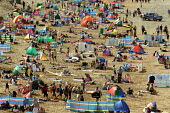 Holidaymakers on Fistral Beach, Newquay - Justin Tallis - 2000s,2005,bathing,Beach,BEACHES,bustling,Busy,coast,coastal,coasts,crowded,eni environmental issue,f,Families,family,grouped,groups,heat,holiday,holiday maker,holiday makers,holidaymaker,holidaymaker