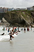 Children playing in the waves on the beach in Newquay - Justin Tallis - 2000s,2005,Beach,BEACHES,board,boarding,bodies,body,boogie,Busy,child,CHILDHOOD,children,coast,coastal,coasts,crowded,eni environmental issue,heat,holiday,holiday maker,holiday makers,holidaymaker,hol