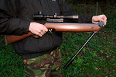 Hunter loading his air rifle in preparation to fire. Caerleon, South Wales - Justin Tallis - 2000s,2005,air rifle,armed,barrel,Bullet,Bullets,country,countryside,Evening,Gun,guns,hobbies,hobby,hobbyist,holding,holds,hunter,hunters,Hunting,LFL leisure,load,Loading,Outdoor,outdoors,outside,pell