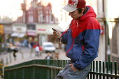 Man using a mobile phone that is hung around his neck by a lanyard. Newport, South Wales - Justin Tallis - 14-11-2005